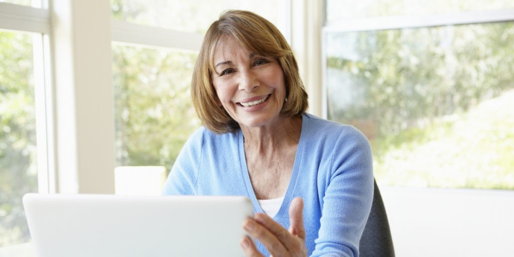 middle aged woman in office with laptop